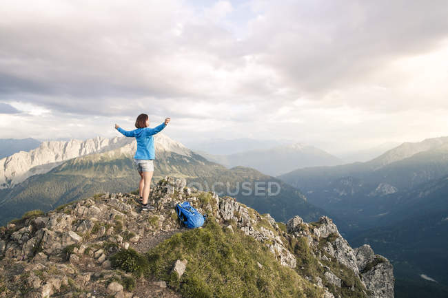 Austria, Tyrol, woman on a hiking trip in the mountains cheering on peak — Stock Photo