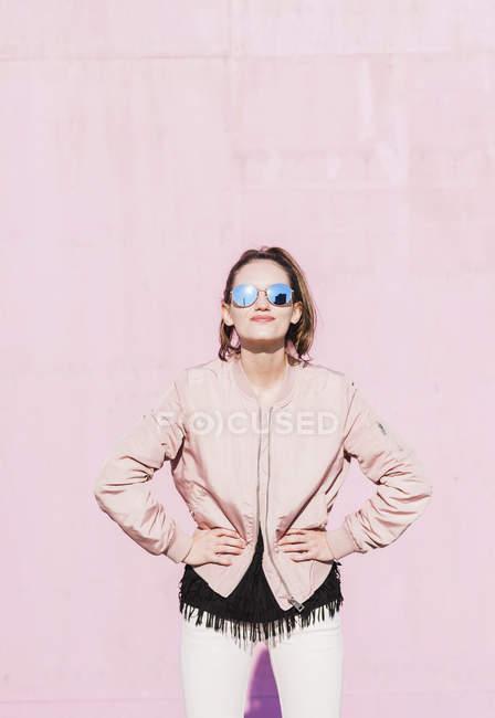 Портрет молодой женщины в солнечных очках и позирующей перед розовой стеной — стоковое фото