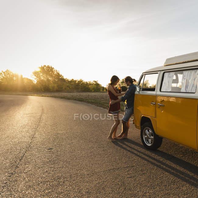 Счастливая пара отдыхает в дороге, выпивает на закате — стоковое фото