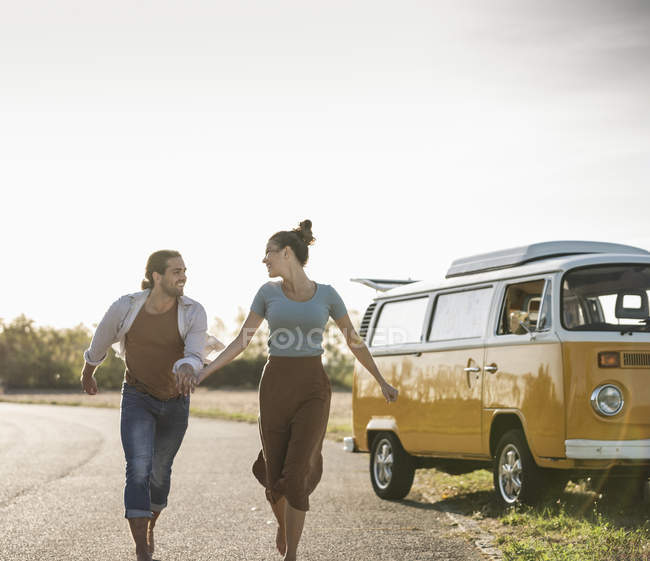 Happy couple doing a road trip with a camper, holding hands on the road — Stock Photo