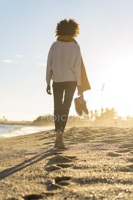 Mujer descalzo en la playa, llevando sus zapatos - foto de stock