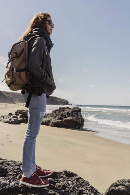 España, Islas Canarias, Fuerteventura, joven con mochila de pie en la playa mirando a la distancia - foto de stock