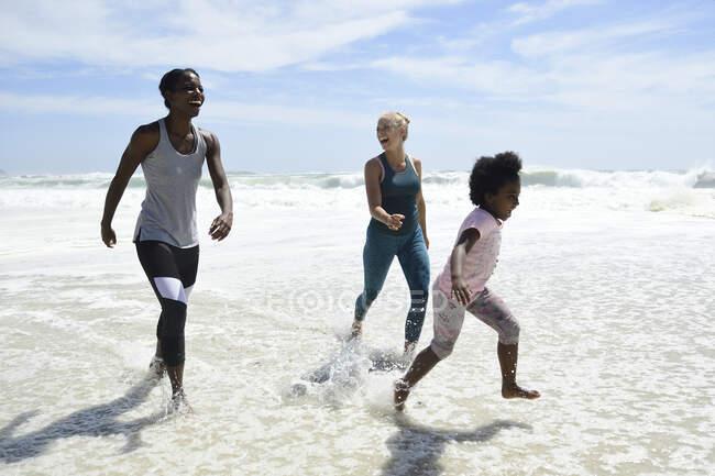 Мать с дочерью и другом развлекаются серфингом на пляже — стоковое фото
