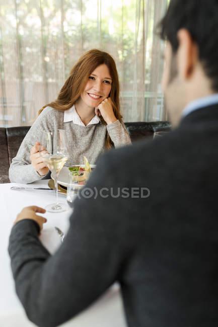 Усміхнена жінка дивиться на людину в ресторані — стокове фото