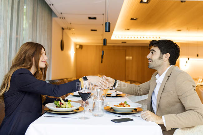 Smiling man and woman shaking hands in a restaurant — Stock Photo
