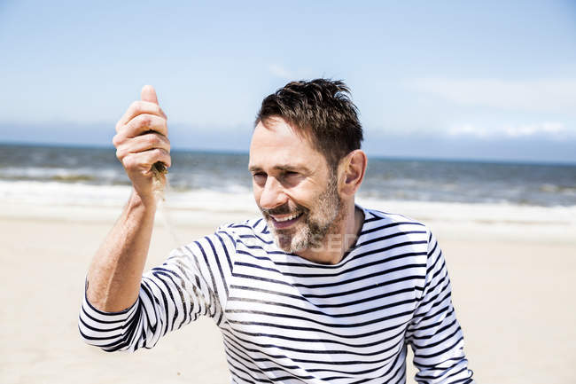 Happy man on the beach letting sand trickling through his hands — Stock Photo