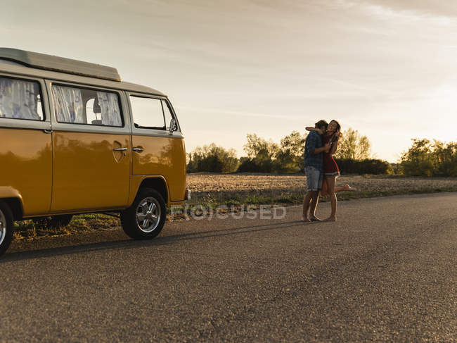 Happy couple doing a road trip with a camper, laughing and embracing on the road — стокове фото