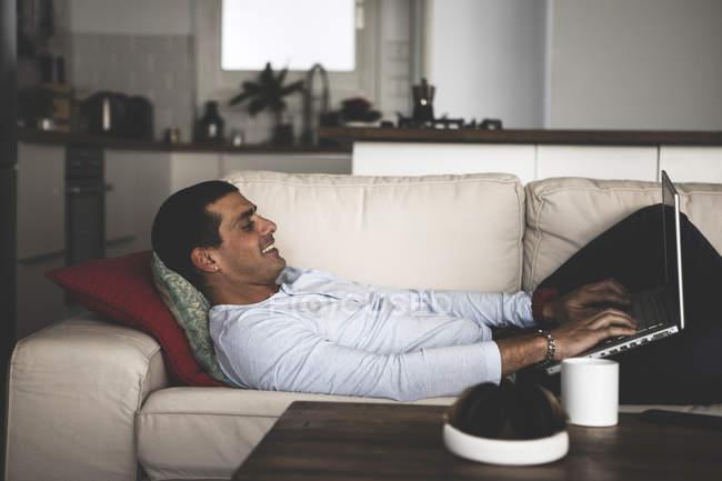 Jeune homme souriant couché sur le canapé à la maison en utilisant un ordinateur portable — Photo de stock