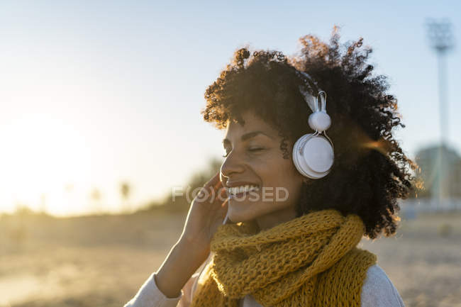 Woman with yellow scarf, listening music on the beach — Stock Photo