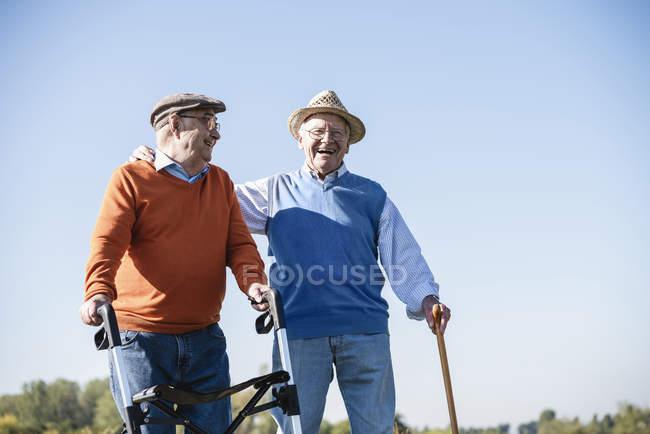 Alte Freunde spazieren mit Gehstock und Rollator durch die Felder und erzählen von alten Zeiten — Stockfoto