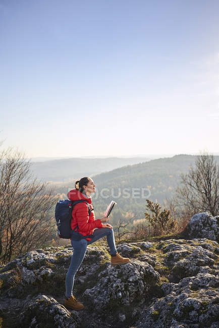 Woman on a hiking trip in the mountains holding map and enjoying beautiful view — Photo de stock