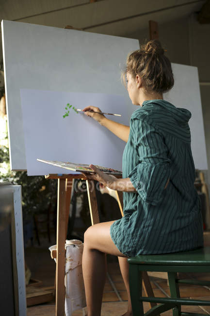Young woman painting in her atelier — Stock Photo