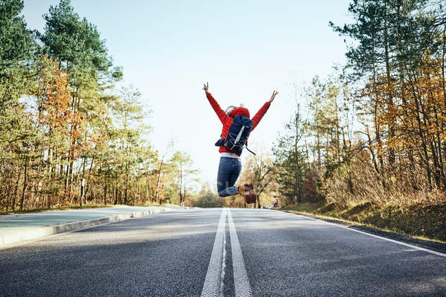 Cheerful woman jumping on an empty road during backpacking trip — Stock Photo