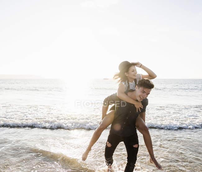 França, Bretanha, jovem feliz carregando namorada piggyback na praia — Fotografia de Stock