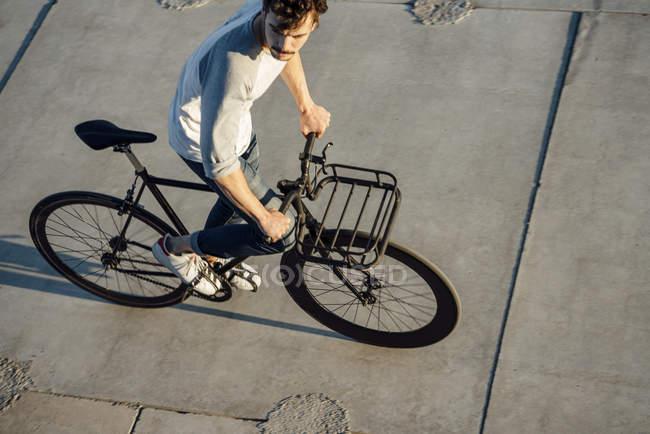 Jovem montando pendulares fixie bicicleta em lajes de concreto — Fotografia de Stock