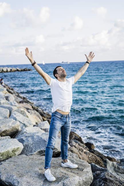 Людина з піднятими руками і очима закриті перед морем — стокове фото