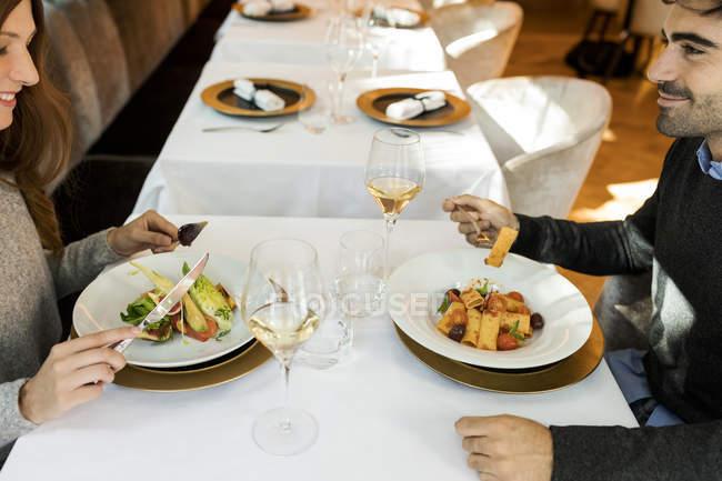 Усміхнена пара їсть стартер в ресторані — стокове фото