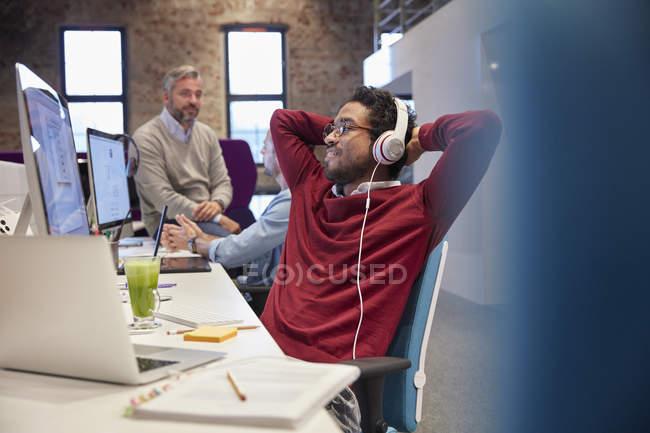Jovem sentado na mesa no escritório, usando fones de ouvido, sorrindo — Fotografia de Stock