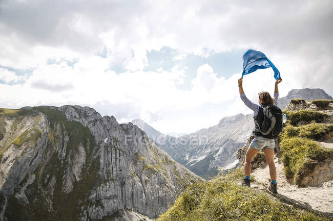 Austria, Tyrol, woman on a hiking trip in the mountains holding cloth — Stock Photo