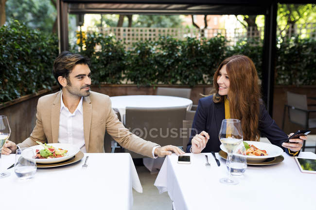 Smiling woman and man with cell phone in a restaurant — Stock Photo