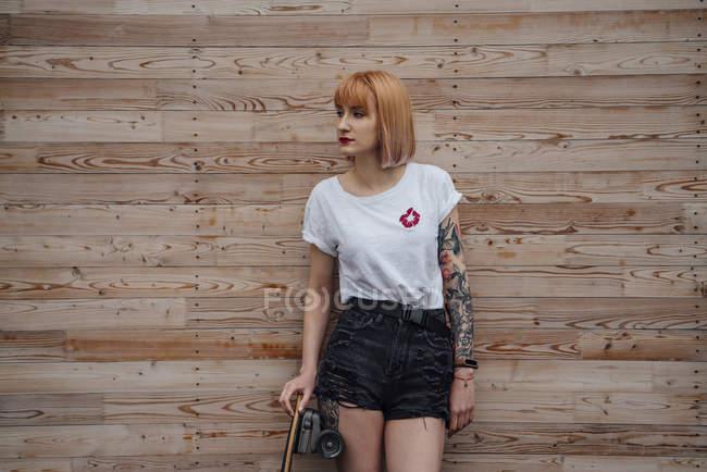 Junge Frau steht mit Skateboard an Holzwand — Stockfoto