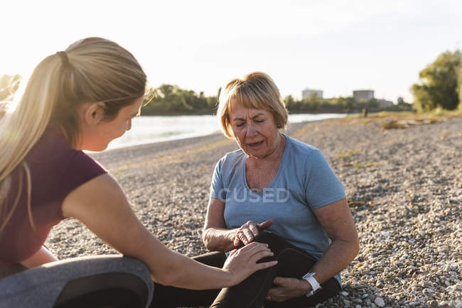 Granddaughter examining aching knee of her grandmother after training at the river — Stock Photo