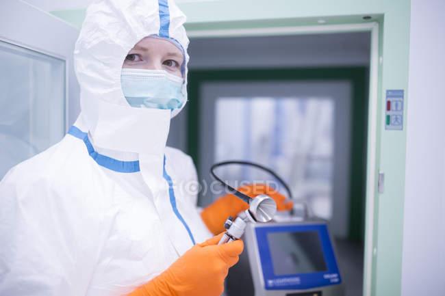 Técnico de laboratorio que lleva un aparato de sujeción general de cuarto limpio en material de podredumbre. - foto de stock