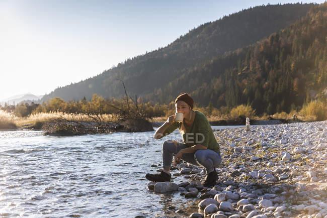 Reife Frau am Flussufer, trinken — Stockfoto