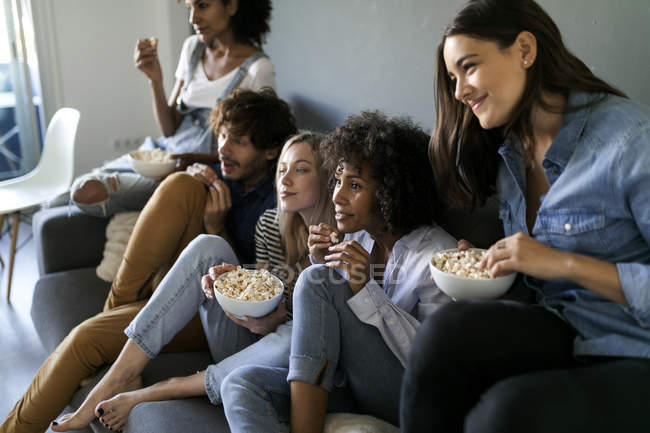 Friends sitting on couch watching tv — Stock Photo