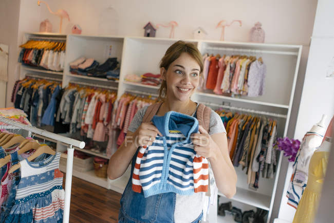 Smiling pregnant woman shopping for baby clothing in a boutique - foto de stock