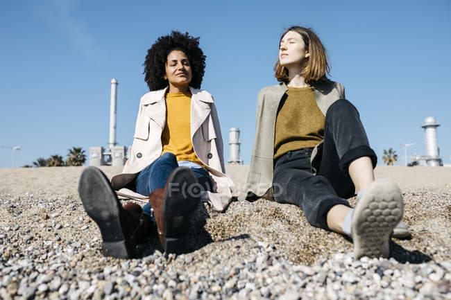 Zwei Freunde sitzen am Strand und genießen ihre Freizeit — Stockfoto