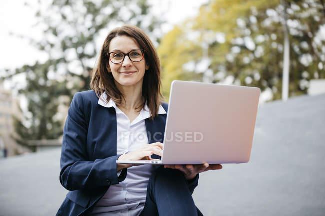 Porträt einer lächelnden Geschäftsfrau in der Stadt mit Laptop — Stockfoto