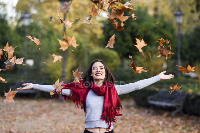 Portrait of laughing young woman with red scarf throwing autumn leaves in the air — Stock Photo