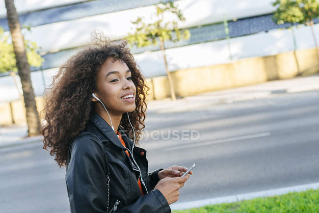 Portrait of smiling young woman listening music with earphones and smartphone — Stock Photo