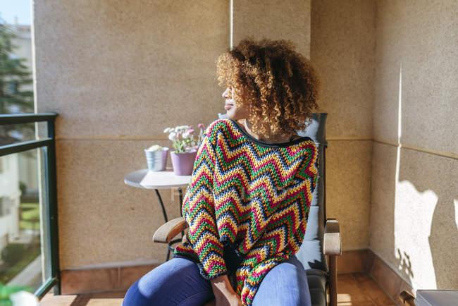 Молода жінка з кучерявим волоссям сидить на балконі під сонцем. — стокове фото