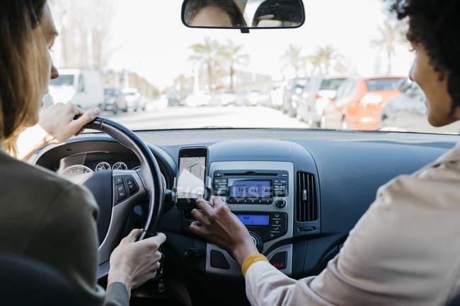 Dos mujeres conduciendo en un coche por la ciudad - foto de stock