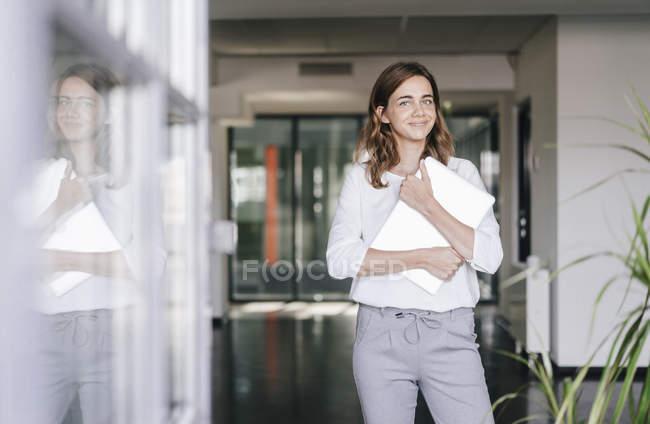 Деловая женщина, стоящая в офисе, держащая ноутбук — стоковое фото