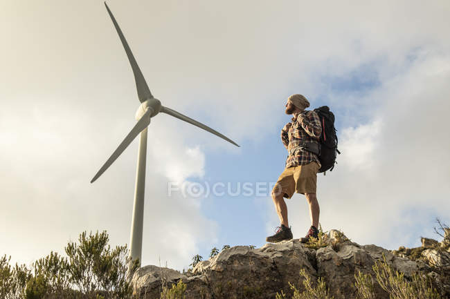 Spain, Andalusia, Tarifa, man on a hiking trip standing on rock with wind turbine in background — Stock Photo