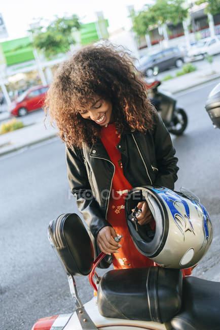 Sorridente giovane donna rimozione blocco di sicurezza dalla sua moto — Foto stock