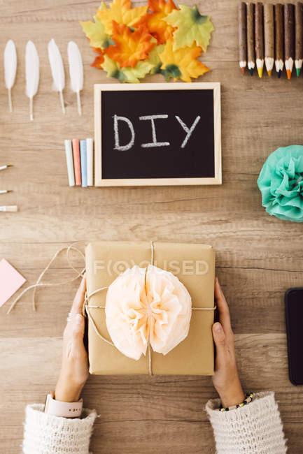 Draufsicht einer jungen Frau, die ein verpacktes Geschenk in ihrem Atelier zeigt — Stockfoto
