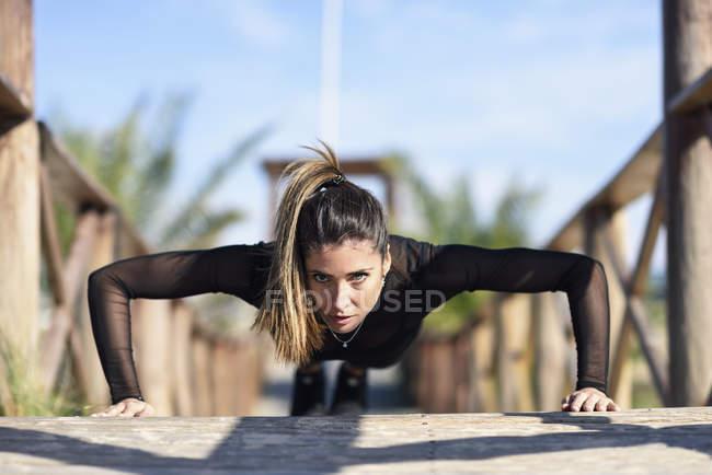 Спортивная женщина отжимается на деревянном мосту — стоковое фото