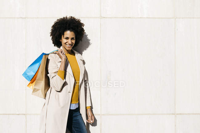 Portrait of smiling woman with shopping bags standing at a wall — Stock Photo