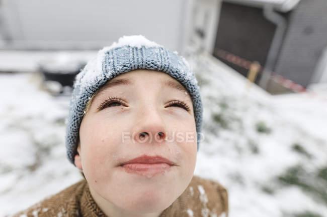 Мальчик смотрит вверх на падающий снег — стоковое фото