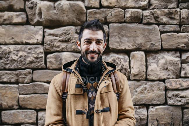 Espanha, Igualada, retrato do homem sorridente na parede de pedra — Fotografia de Stock