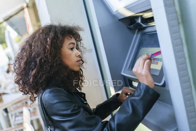 Woman using credit card at ATM — Stockfoto