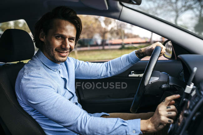 Portrait of smiling businessman driving car using cell phone as navigation system — Photo de stock