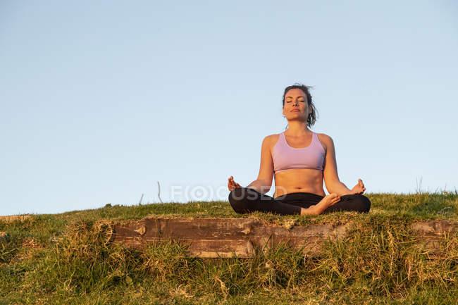 Женщина медитирует на лугу вечером — стоковое фото