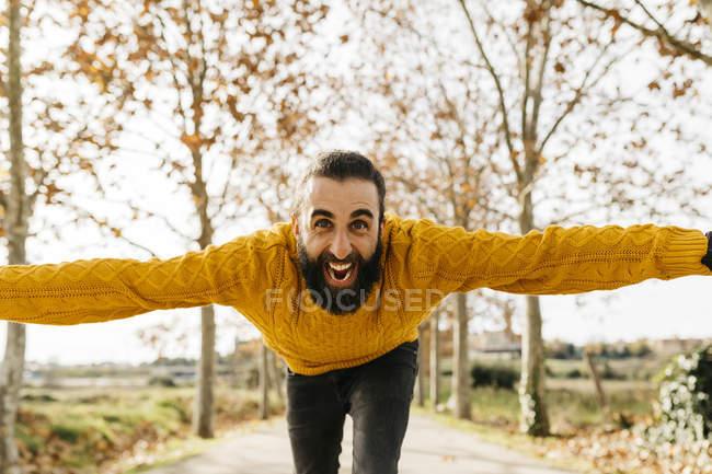 Jeune homme à bras ouverts et heureux dans un parc en automne — Photo de stock