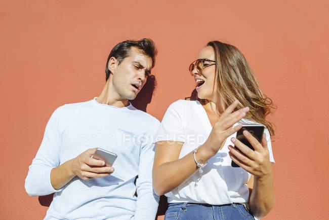 Couple avec téléphones cellulaires à l'extérieur par une journée ensoleillée — Photo de stock