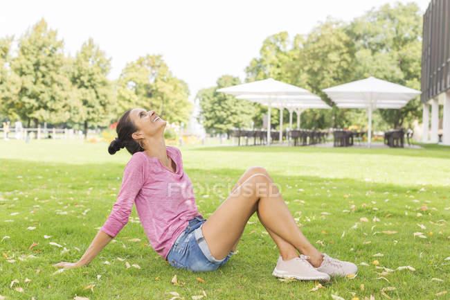 Mulher madura sentada em um prado no verão olhando para o céu — Fotografia de Stock